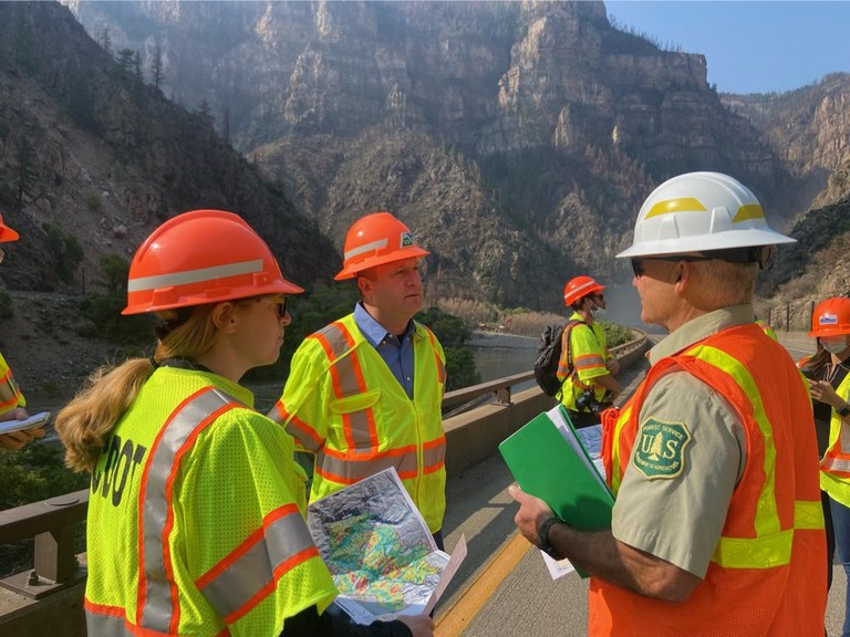 Governor Polis, CDOT Director Lew, State Officials and members of the media observe the damage and repairs