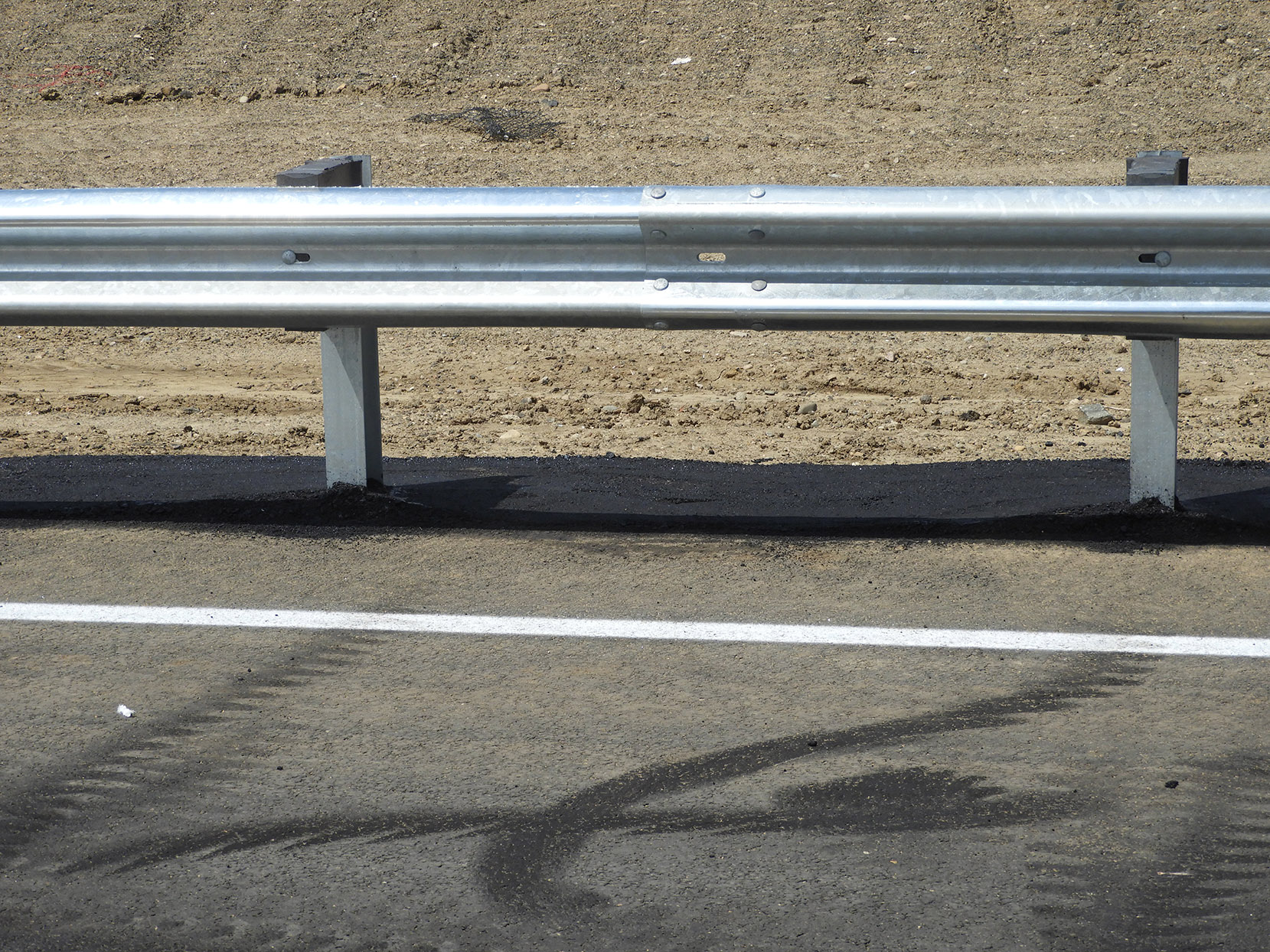 Asphalt around guardrail posts, south of 144th Avenue on the west side of southbound I-25