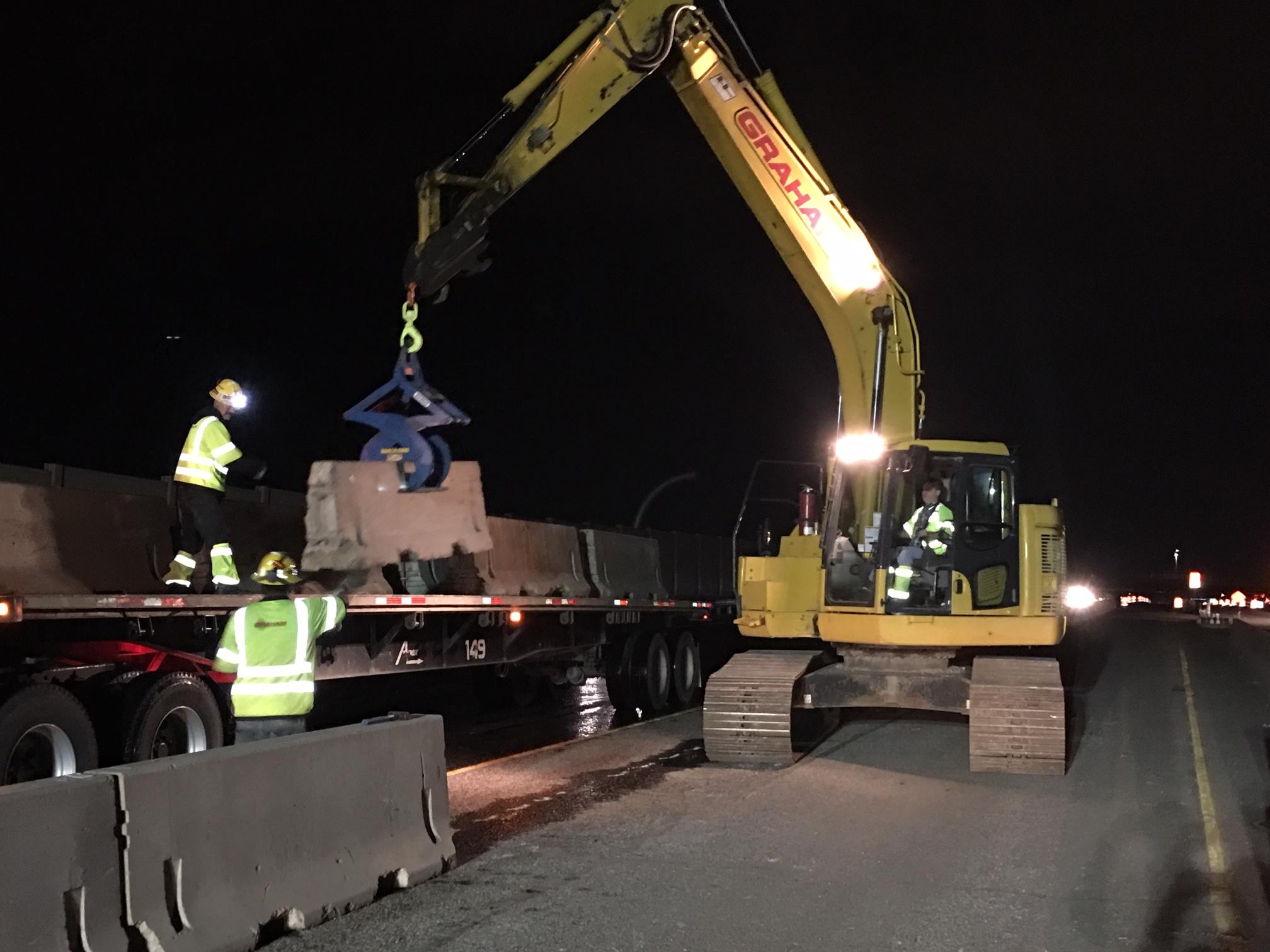Crews installing temporary barrier