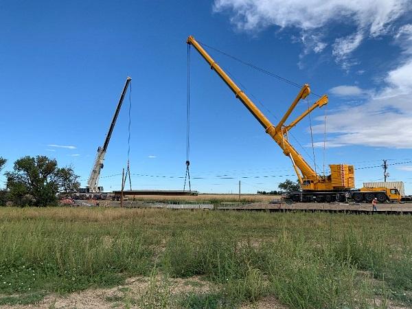 Cranes lifting prepoured bridge deck